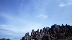 Astrophotography Time Lapse of Stars over Moonlit Rock Formation -Zoom Out- - stock footage