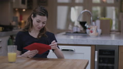 Young adult female opening Valentine's Day Card at Kitchen table Stock Footage