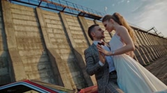 Newlyweds on the background of a dam slowmotion Stock Footage