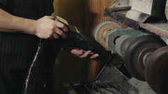 Shoemaker repairs sole of leither boots Stock Footage