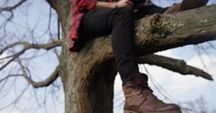 4K Young casual man sitting in a tree & looking at smartphone Stock Footage
