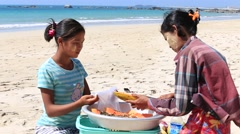Women selling fruits at the shoreline to tourists in Ngapali beach. Myanmar Stock Footage