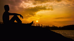 The man sit against the background of sunset. Time lapse. Wide angle - stock footage