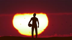 The man stand with a ball against the background of sunset. Time lapse Stock Footage