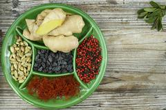 Green board with red saffron, raisins, cardamom, pepper and fresh ginger - stock photo
