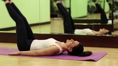 Woman trains in gym. Woman lies on the mat and pumps abdominal muscles Stock Footage