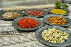Cardamom, red saffron,- spices and herbs in metal bowls. - stock photo