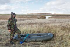 Hunter pumps up an inflatable boat - stock photo