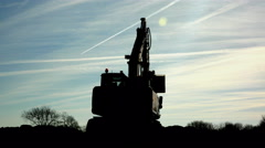 Big excavator (bulldozer) silhouette moving against a blue background sky Stock Footage