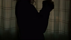 Young woman sips a cup of tea in a dark room, she likes loneliness Stock Footage