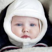 Infant boy is lying in a stroller in winter clothes Stock Photos
