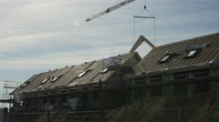 Constructing houses with a large crane, putting roof on the houses Stock Footage