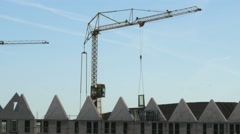 Constructing houses with a large crane, putting windows in the houses - stock footage