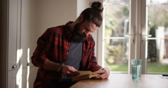 4K Portrait of casual man relaxing at home, completely engrossed in a book Stock Footage