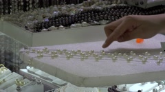 Craftswoman glues the pearls on a necklace at HongQiao Pearl Market. Beijing Stock Footage