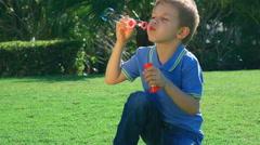 Little boy blowing soap bubbles. Full HD Video - stock footage