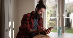 4K Serious casual man at home, concentrating as he uses computer tablet - stock footage