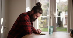4K Serious casual man at home, concentrating as he uses computer tablet Stock Footage