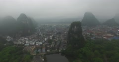 AERIAL PAN SHOT OF YANGSHUO CITY CENTER WITH FOG AND MOUNTAINS - CHINA Stock Footage