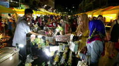 KRABI, THAILAND crowded night market two woman wearing  hijabs pay money Stock Footage