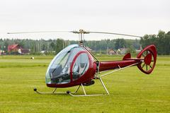 Small private helicopter on grass - stock photo
