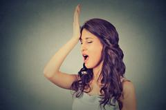 Regrets wrong doing. Woman, slapping hand on head having duh moment - stock photo