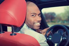 handsome young man in new car driving - stock photo