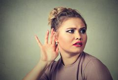 Closeup portrait young nosy woman hand to ear gesture, trying carefully inten Stock Photos