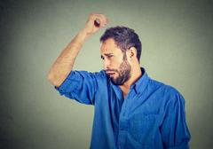 Young man, smelling, sniffing his armpit, something stinks, very bad, foul od Stock Photos