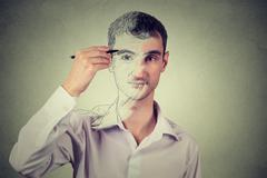 Young man drawing self portrait face, hiding true emotion isolated on grey wa Stock Photos