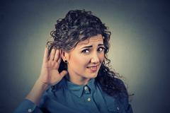 unhappy hard of hearing woman placing hand on ear asking someone to speak up - stock photo
