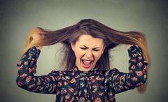 Very angry woman pulling her hair out screaming - stock photo