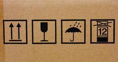 Shipping icons on cardboard box - stock photo