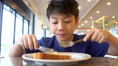 Asian preteens Boy eats bread sitting at the table , 4K Stock Footage