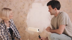 Adult couple painting wall in new home Stock Footage