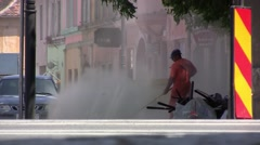 Worker stirs clouds of dust on the road with a compressor blowing dirt accumulat Stock Footage