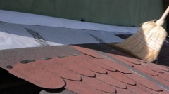 Worker who give sweep over bituminous shingle placed on the roof of a shed - stock footage