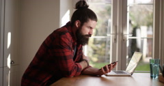 4K Casual man at home looking at smartphone with laptop open in front of him Stock Footage