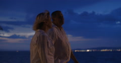 Senior people having walk along the sea at night Stock Footage
