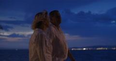 Senior people having walk along the sea at night - stock footage