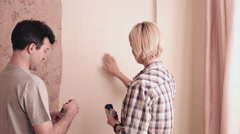 Adult couple painting wall in new home - stock footage