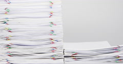 Stack overload paper on white table time lapse Stock Footage