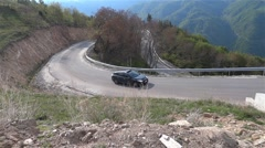 Tractor pulling a trailer full of the wood on a paved road that climbs winding - stock footage