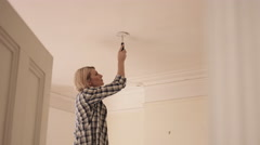 Adult Woman installing smoke detector in home - stock footage