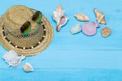 Seashells, hat and sunglasses on blue wooden background - stock photo