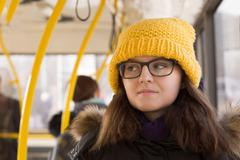 Young woman in yellow cap riding  public transport - stock photo
