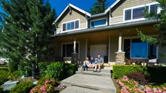 Happy family of four sitting on the porch in front of their home - stock footage