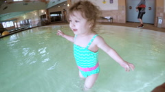 Toddler girl swimming at indoor swimming pool. Stock Footage
