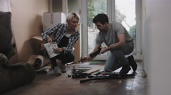 Couple putting together flatpack shelving Stock Footage