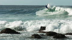 spectators watch a surfer riding a wave at snapper rocks - stock footage